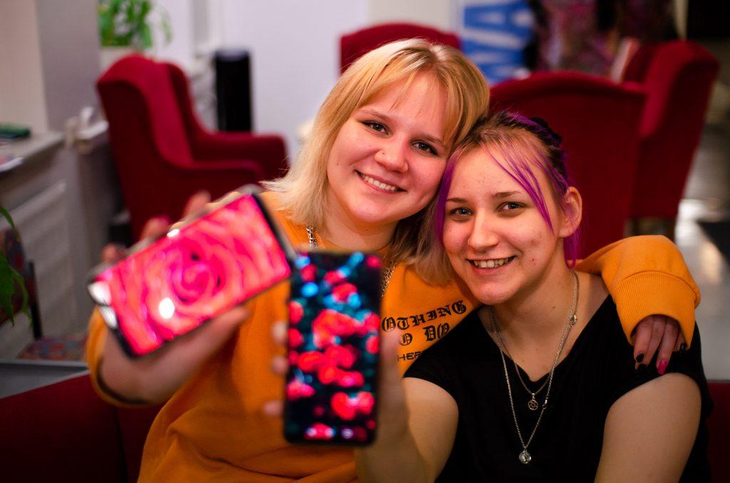Kuvassa on kaksi nuorta naista vierekkäin, jotka ojentavat puhelimiaan kameraa kohti.