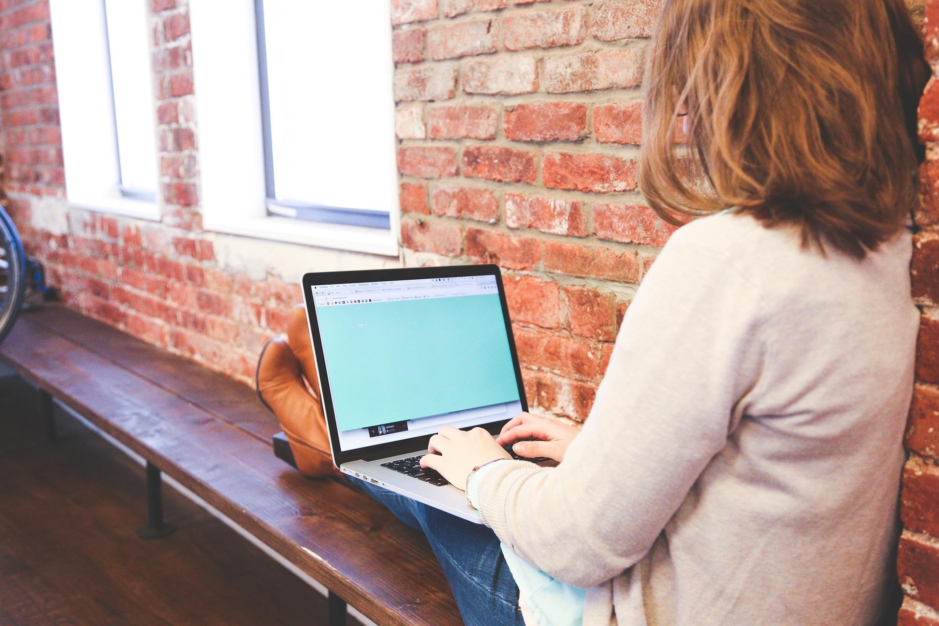 Kuvassa nuori nainen istuu penkillä ja pitää sylissään tietokonetta.