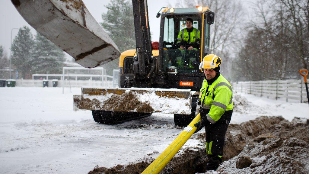 Mies asentaa valokuituputkea kaivinkoneen kaivamaan ojaan. Ensilumi on peittänyt routaisen maan.