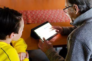 Poika ja isoisä katselevat tablettia joka valaisee isoisän kasvot.