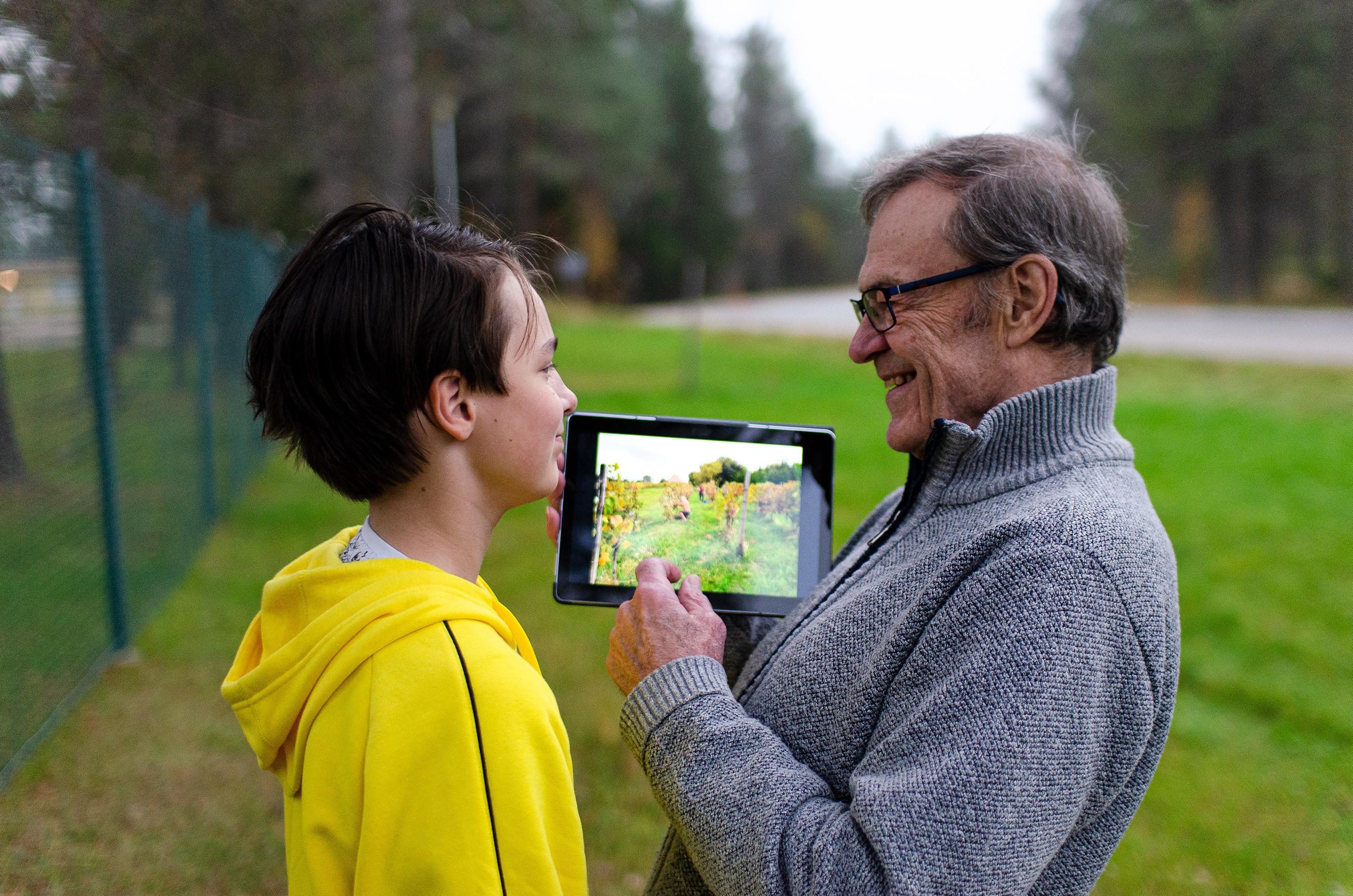Kuvassa isosisä ja poika katsovat tablettia ulkona